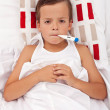 Stock Photo: Sick child in bed with thermometer