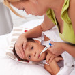 Woman checking little boy's temperature — Stock Photo #7113471