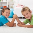 Постер, плакат: Happy boys laughing and arm wrestling