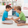 Kids wrestling on the floor - Stock Photo