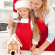 Happy woman and little girl making gingerbread house — Stock Photo