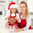 Christmas woman and little girl making gingerbread cookies — Stock Photo
