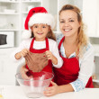 Royalty-Free Stock Photo: Christmas woman and little girl making gingerbread cookies
