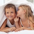 Kids sharing their secrets under the quilt — Stock Photo