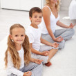 Kids doing yoga relaxation with their mother — Stock Photo #7113598