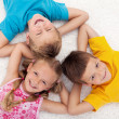 Three kids laying on the floor in circle - Stock Photo