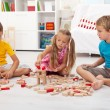 Three kids playing with wooden blocks — ストック写真