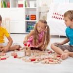 drie kinderen spelen met houtblokken — Stockfoto