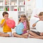 Kids blowing large balloons — Stock Photo