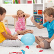 Kids popping balloons - Stock Photo