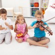 Stock Photo: Kids trying to play on different musical instruments
