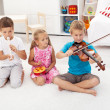 Kids trying to play on different musical instruments - Stock Photo