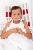 Sick child in bed with thermometer — Stock Photo