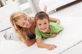 Gelukkig moeder en zoon spelen in de woonkamer — Stockfoto