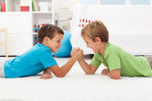 Boys arm wrestling in the kids room — Стоковое фото