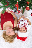 Woman and little girl under the christmas tree — Stock Photo