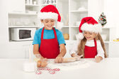 Niños felices navidad estirar la masa para galletas — Foto de Stock