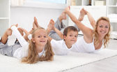 Family doing stretching exercises at home — Stock Photo