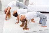 Woman and kids doing gymnastic exercises at home — Stock Photo
