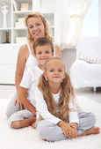 Happy woman and kids sitting in the living room — Stock Photo