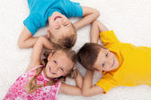 Three kids laying on the floor in circle — Stock Photo