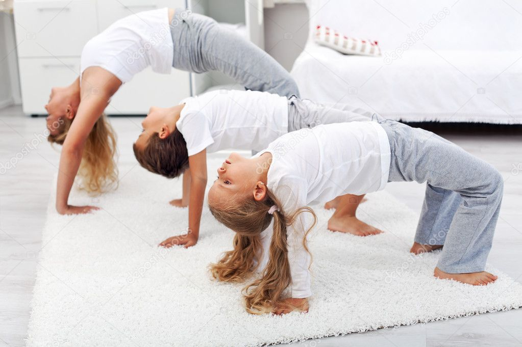 Woman and kids doing bridge stretch gymnastic exercises at home — Stock Photo #7113612