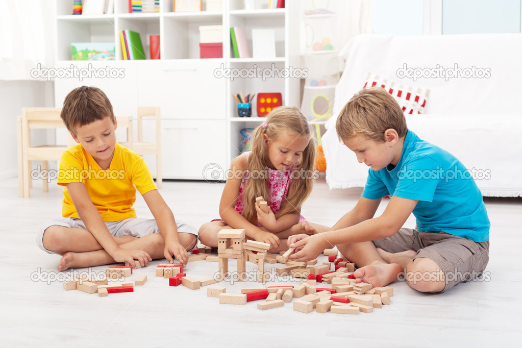 Three kids playing with wooden blocks sitting on the floor — Stock Photo #7113712