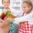 Kids unpacking vegetables in the kitchen — Stock Photo