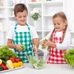 Kids in the kitchen preparing salad — Stock Photo