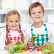 Happy kids preparing a meal in the kitchen — Stock Photo