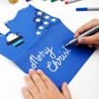 Child writing christmas greeting card — Stock Photo