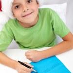 Happy kid writing letter to santa — Stock Photo