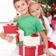Siblings with lots of presents at christmas time — 图库照片