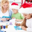 Family making seasonal greeting cards together — Stock Photo #7539772