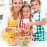 Happy family preparing fresh salad — Stock Photo #7539876