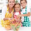 Happy family preparing fresh salad — Stock Photo