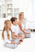 Family sitting in a row meditating — Stock Photo