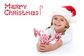 Little girl with lots of candy canes — Stock fotografie