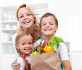 Happy family with the groceries — Stock Photo