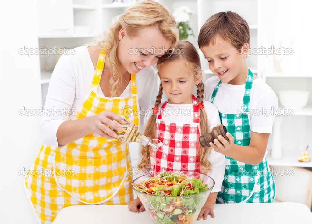 Family in the kitchen seasoning the fresh vegetables salad  Stock Photo #7539883