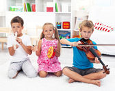 Kids playing on musical instruments — Stock Photo