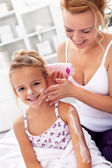 Body care - woman and little girl applying cream — Stock Photo
