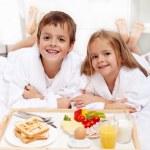 Happy kids having breakfast in bed — Stock Photo
