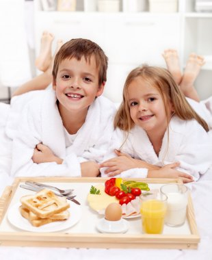 Depositphotos 7727528 happy kids having breakfast in bed jpg