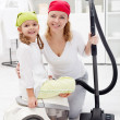 Cleaning day - woman and little girl with vacuum cleaner — Stock Photo