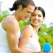 Young happy smiling couple in sport wear doing fitness exercise — Stock Photo