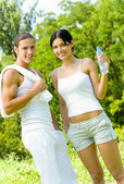 Young happy smiling couple with bottle of water in sport wear on workout — Stock Photo