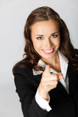 Business woman pointing finger at viewer, over grey — Stock Photo