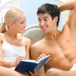 Young attractive happy smiling couple with notebook in bedroom — Stock Photo #6763750