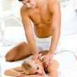 Young happy couple making massage in bedroom — Stock Photo